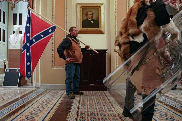 A supporter of President Donald Trump carries a Confederate battle flag inside the Capitol building in Washington, as a mob of his supporters protest the presidential election results, on Wednesday, Jan. 6, 2021. Historians said it was unnerving to see a man carry the flag inside the Capitol, something not even Confederate soldiers were able to do during the Civil War. (Erin Schaff/The New York Times)