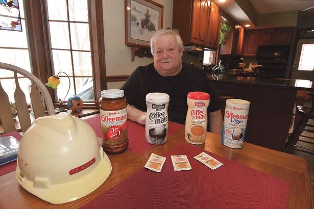 Tom Schierl shows mementos from his 43-year career at the Carnation, then Nestle, plant in Jacksonville. These items and others have been donated to the Jacksonville Area Museum.