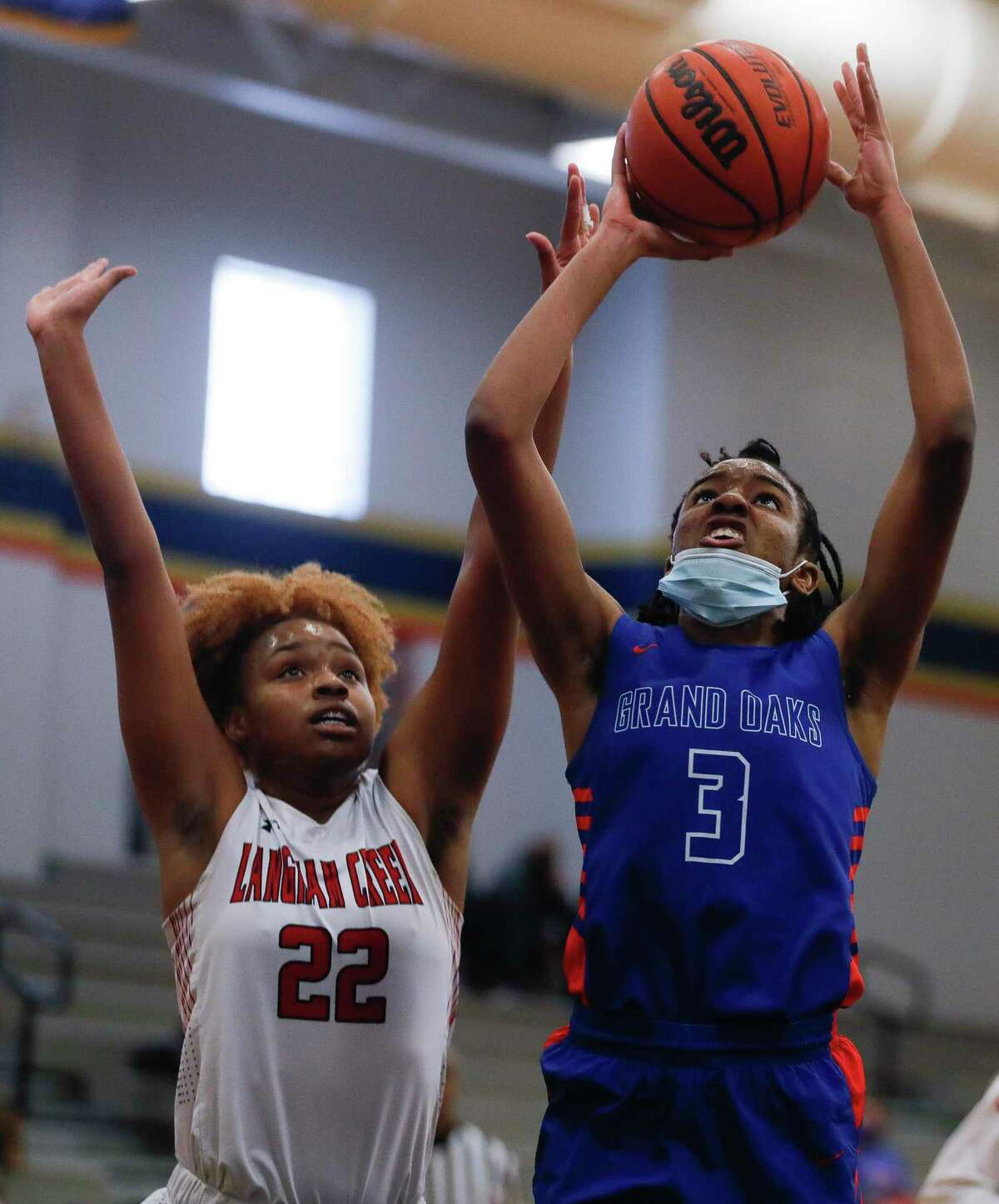 Grand Oaks center Ngozi Agoh (3) shoots past Langham Creek forward Saija Cleveland (22) during the first quarter of a Region II-6A area girls basketball playoff game at Klein Collins High School, Saturday, Feb. 20, 2021, in Spring.