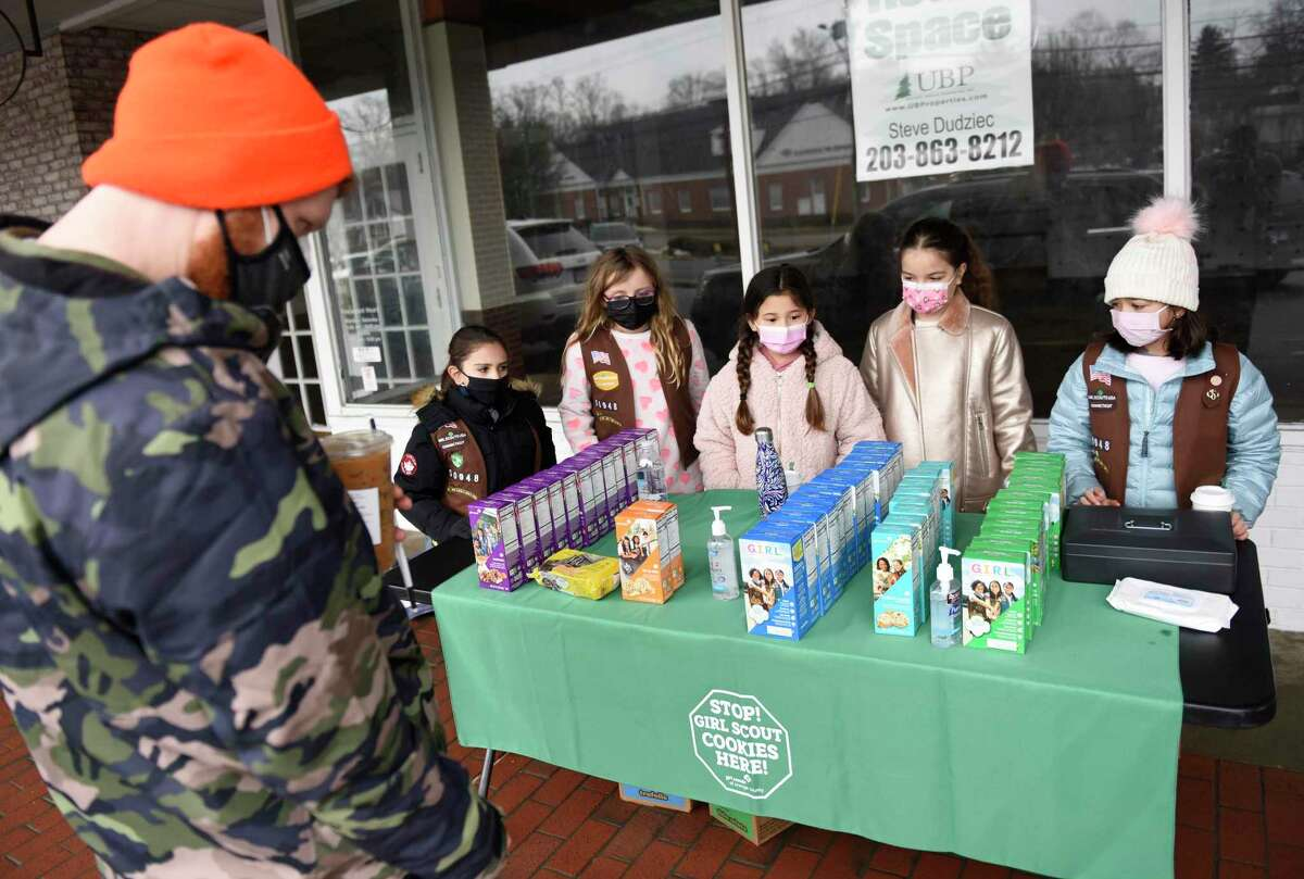 North Stamford Girl Scouts Troop 50948 members, from left, Adela Perez, 9, Ella Broggi, 8, Maya Hughes, 9, Emma Podlastina, 8, and Victoria Shaw, 9, sell cookies at High Ridge Center in Stamford, Conn. Sunday, Feb. 28, 2021. Sunday's sale was the first cookie booth of the year in Stamford.