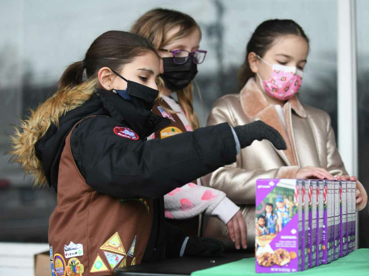 North Stamford Girl Scouts Troop 50948 members Adela Perez, 9, left, Ella Broggi, 8, center, and Emma Podlastina, 8, sell cookies at High Ridge Center in Stamford, Conn. Sunday, Feb. 28, 2021. Sunday's sale was the first cookie booth of the year in Stamford.