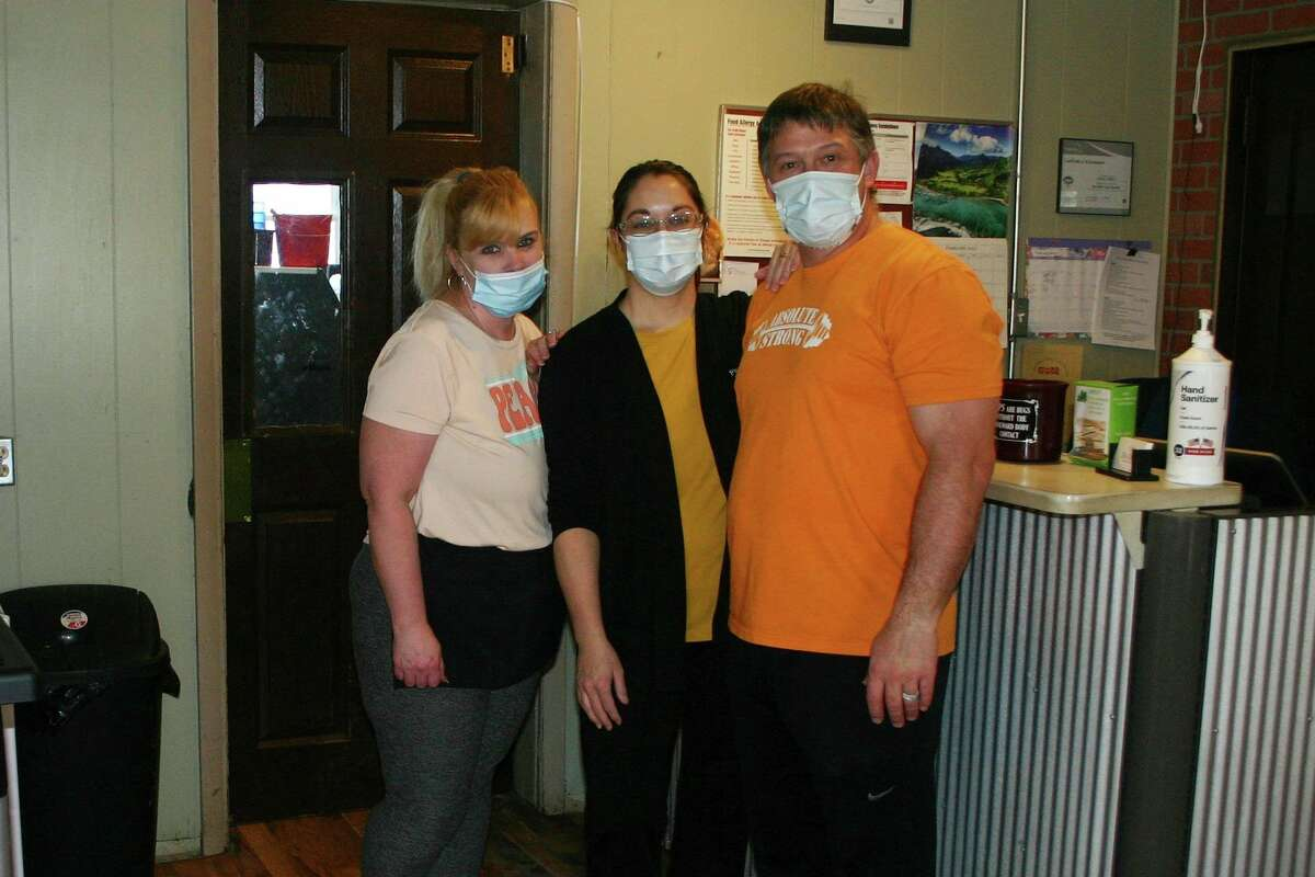 Deerdra Sims, center, with her husband and a member of her wait staff, eagerly await customers since they fully reopened with the help of a $4,000 MEDC small business survival grant award. (Pioneer photo/Cathie Crew)