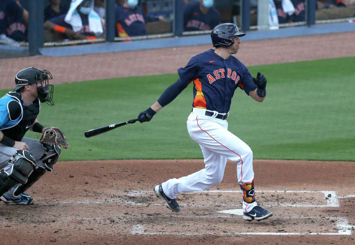 Houston Astros catcher Jason Castro (18) hits an RBI single, scoring Kyle Tucker during the first inning of an MLB spring training game at Ballpark of the Palm Beaches in West Palm Beach, Florida, Sunday, February 28, 2021.