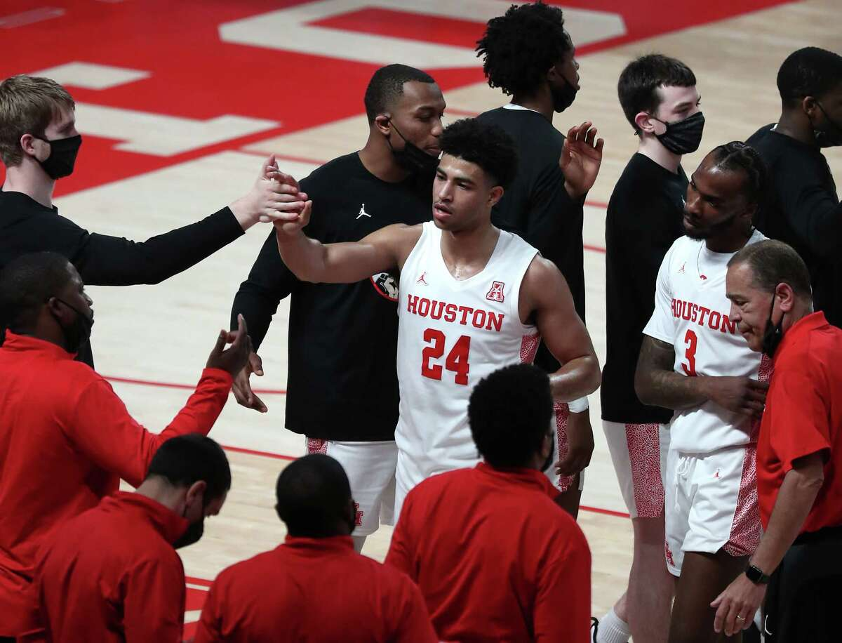 Houston guard Quentin Grimes (24) high fives his teammates as he comes off the court during a time out in the first half on an NCAA basketball game against South Florida Sunday, Feb. 28, 2021, at Fertitta Center in Houston.