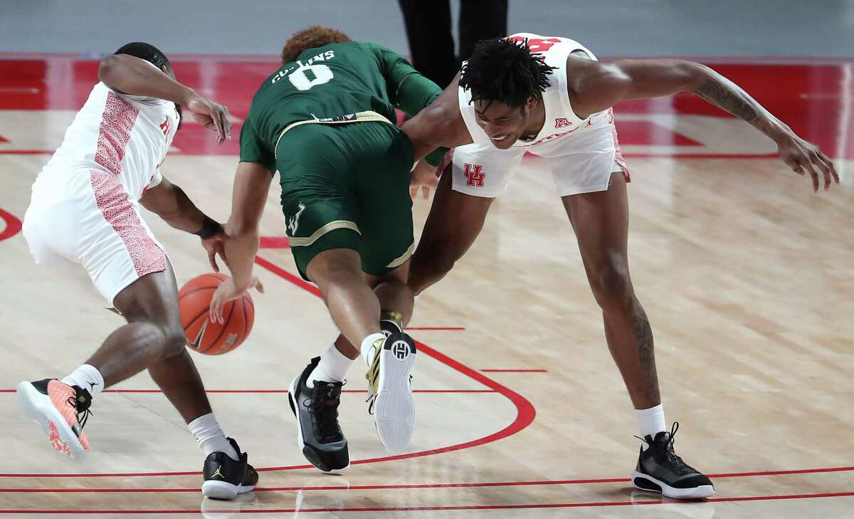 South Florida guard David Collins (0) is tripped up by Houston guard Jamal Shead (1) and forward Brison Gresham (55) as he tries to dribble between them during the first half on an NCAA basketball game Sunday, Feb. 28, 2021, at Fertitta Center in Houston.