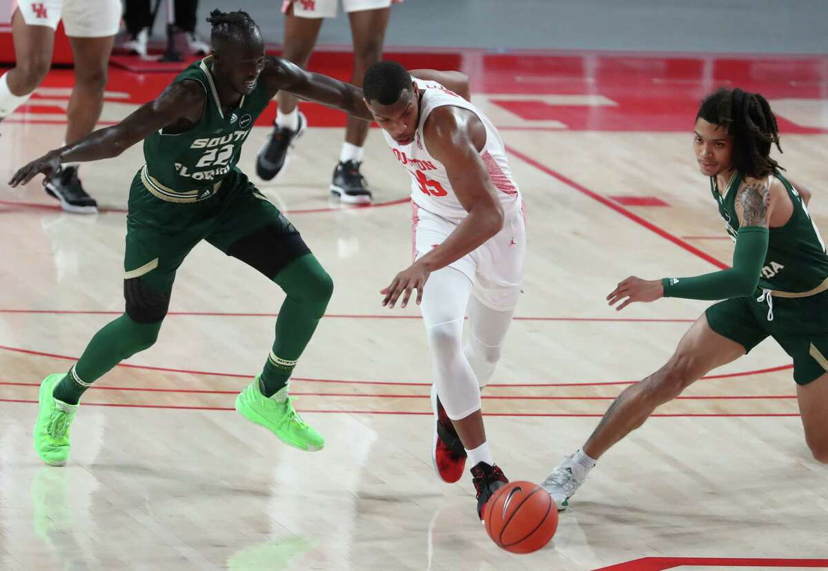 Houston forward Fabian White Jr. (35) steals the ball from South Florida forward Madut Akec (22) during the first half on an NCAA basketball game Sunday, Feb. 28, 2021, at Fertitta Center in Houston.