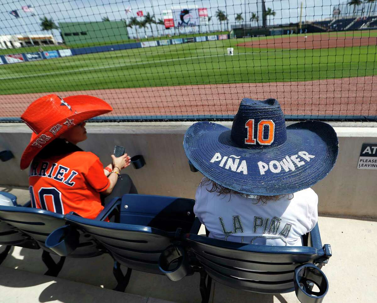 Fans of Houston Astros Yuli Gurriel wear hats with his number on them as they waited for the game to begin before an MLB spring training game at Ballpark of the Palm Beaches in West Palm Beach, Florida, Sunday, February 28, 2021.