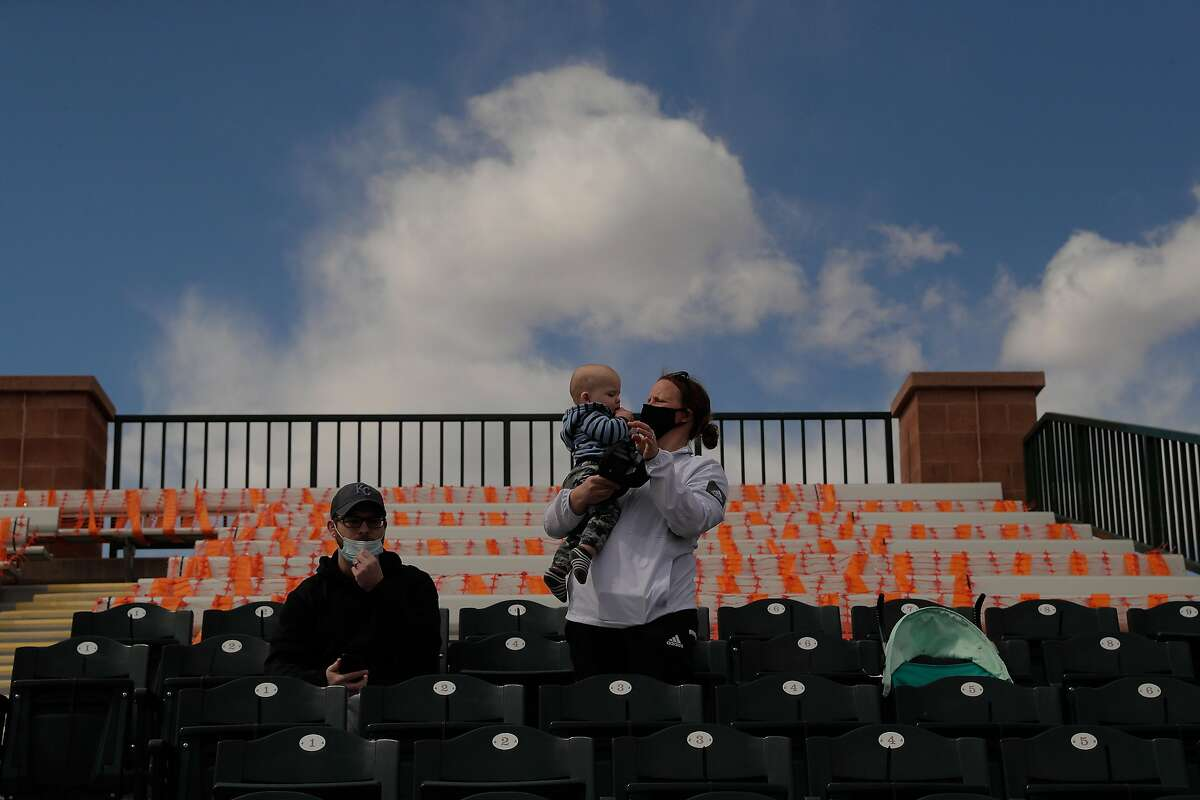 Kyle and Justine Wichman sit in the stands with their baby son Grady, 10 months old, before the Giants faced the Angels at Scottsdale Stadium on Feb. 28.