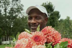 Leaford Roberts of Bear Creek Farm with fresh-picked Ferncliff Copper dahlias.