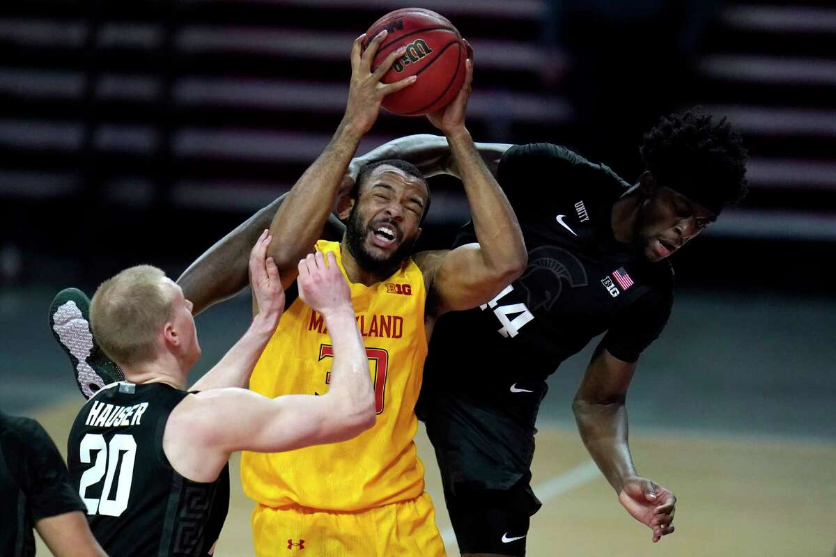 Maryland forward Galin Smith, center, is fouled while going up for a shot against Michigan State forward Gabe Brown, right, and forward Joey Hauser during the second half of an NCAA college basketball game, Sunday, Feb. 28, 2021, in College Park, Md. Maryland won 73-55. (AP Photo/Julio Cortez)