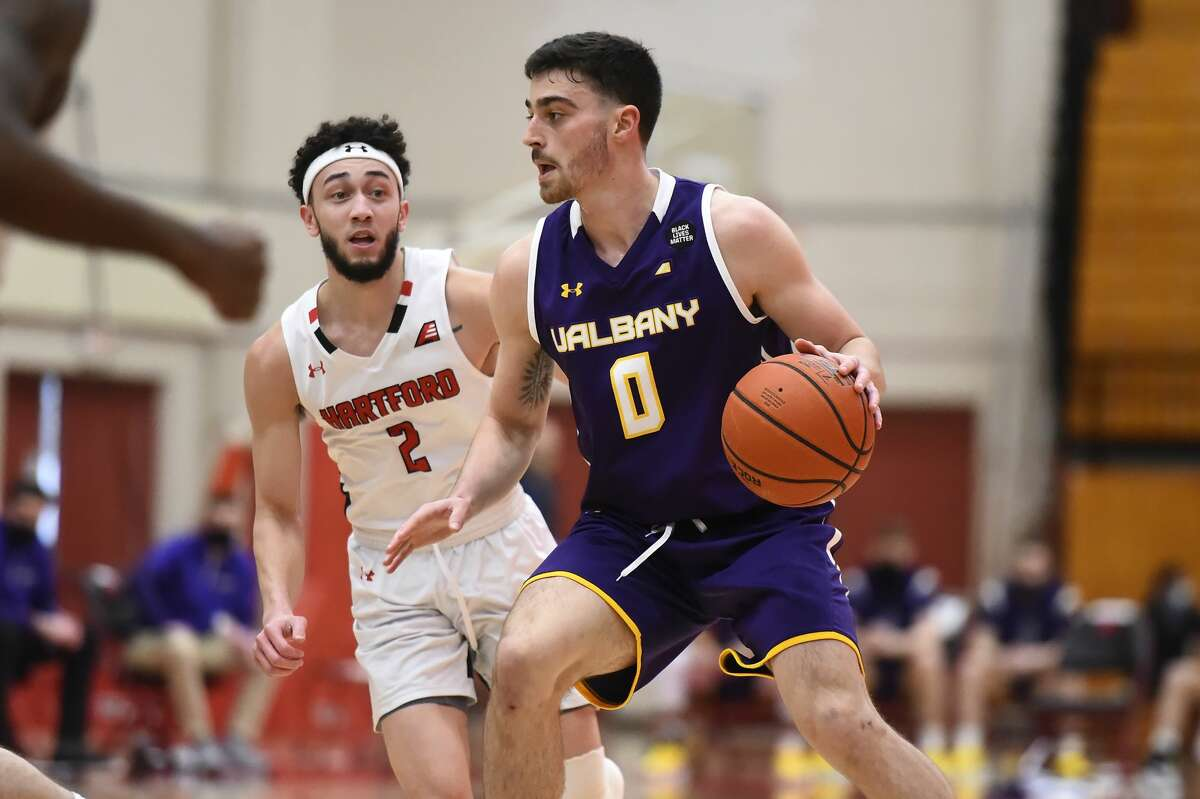 UAlbany captain Antonio Rizzuto (0) drives past Hartford defender D.J. Mitchell in an America East basketball tournament quarterfinal game Sunday, Feb. 28, 2021, at Chase Arena in Hartford, Conn. UAlbany's season ended with an 83-77 loss. (Steve McLaughlin/Hartford athletics)