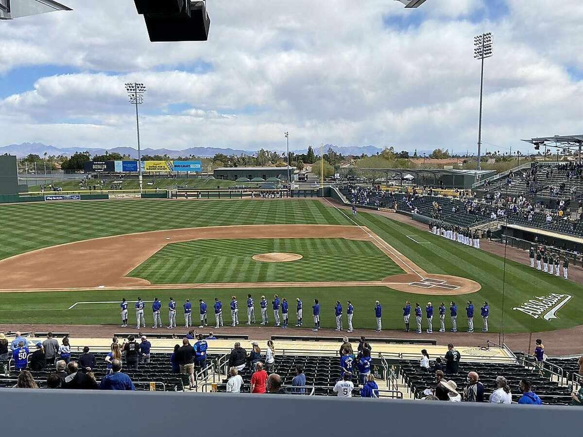 The Oakland A's and Los Angeles Dodgers line up for the national anthem before their Cactus League opener at Hohokam Stadium in Mesa, Ariz., on February 28, 2021