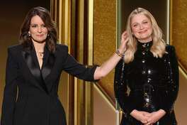 """This handout screen grab courtesy of NBCUniversal shows hosts, Tina Fey (L) and Amy Poehler (R) during the 78th Annual Golden Globe Awards ceremony simultaneously in Beverly Hills, California and in New York on February 28, 2021. - Usually a star-packed, laid-back party that draws Tinseltown's biggest names to a Beverly Hills hotel ballroom, this pandemic edition will be broadcast from two scaled-down venues, with frontline and essential workers among the few in attendance. (Photo by - / NBCUniversal / AFP) / RESTRICTED TO EDITORIAL USE - MANDATORY CREDIT """"AFP PHOTO /NBCUniversal"""" - NO MARKETING NO ADVERTISING CAMPAIGNS - DISTRIBUTED AS A SERVICE TO CLIENTS --- NO ARCHIVE --- / **FOR EDITORIAL USE ONLY AND CANNOT BE ALTERED, ARCHIVED OR RESOLD. SPECIFIC CLEARANCE REQUIRED FOR COMMERCIAL OR PROMOTIONAL USE. CONTACT YOUR NBCU REPRESENTATIVE FOR FURTHER INFORMATION** (Photo by -/NBCUniversal/AFP via Getty Images)"""