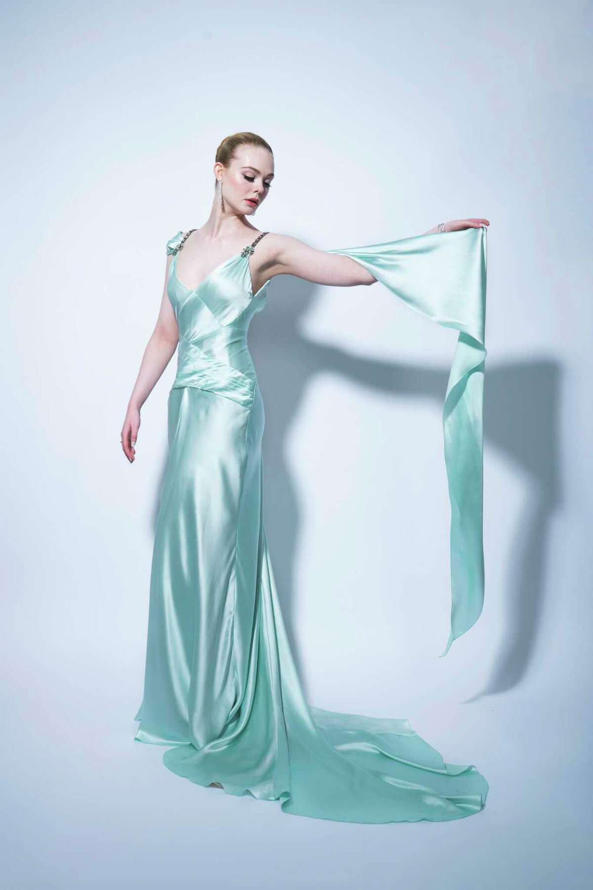 Elle Fanning chose a custom Gucci mint green satin draped gown with embroidered crystal brooches and silver leather high heel platform sandals.