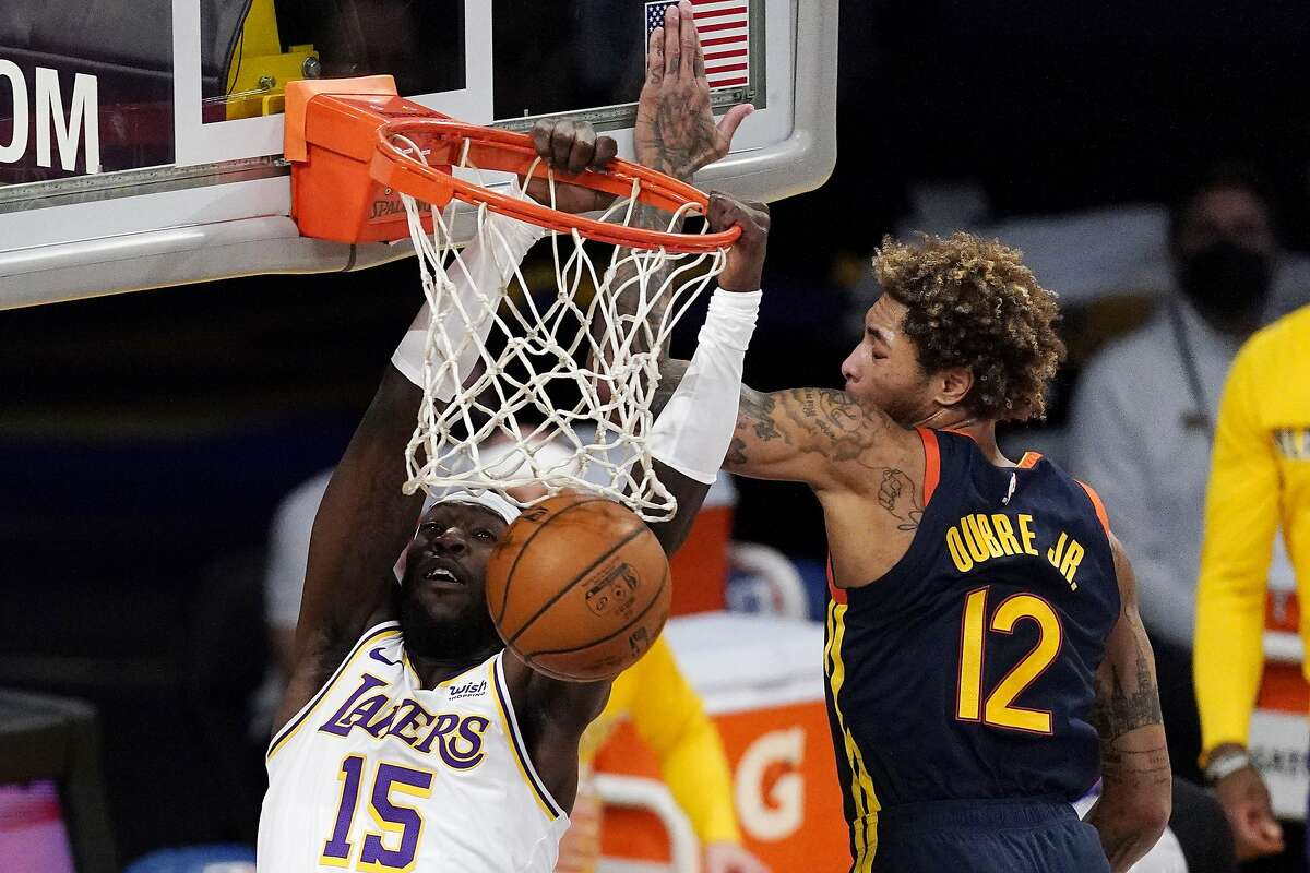 Los Angeles Lakers center Montrezl Harrell, left, dunks as Golden State Warriors guard Kelly Oubre Jr. defends during the first half of an NBA basketball game Sunday, Feb. 28, 2021, in Los Angeles. (AP Photo/Mark J. Terrill)