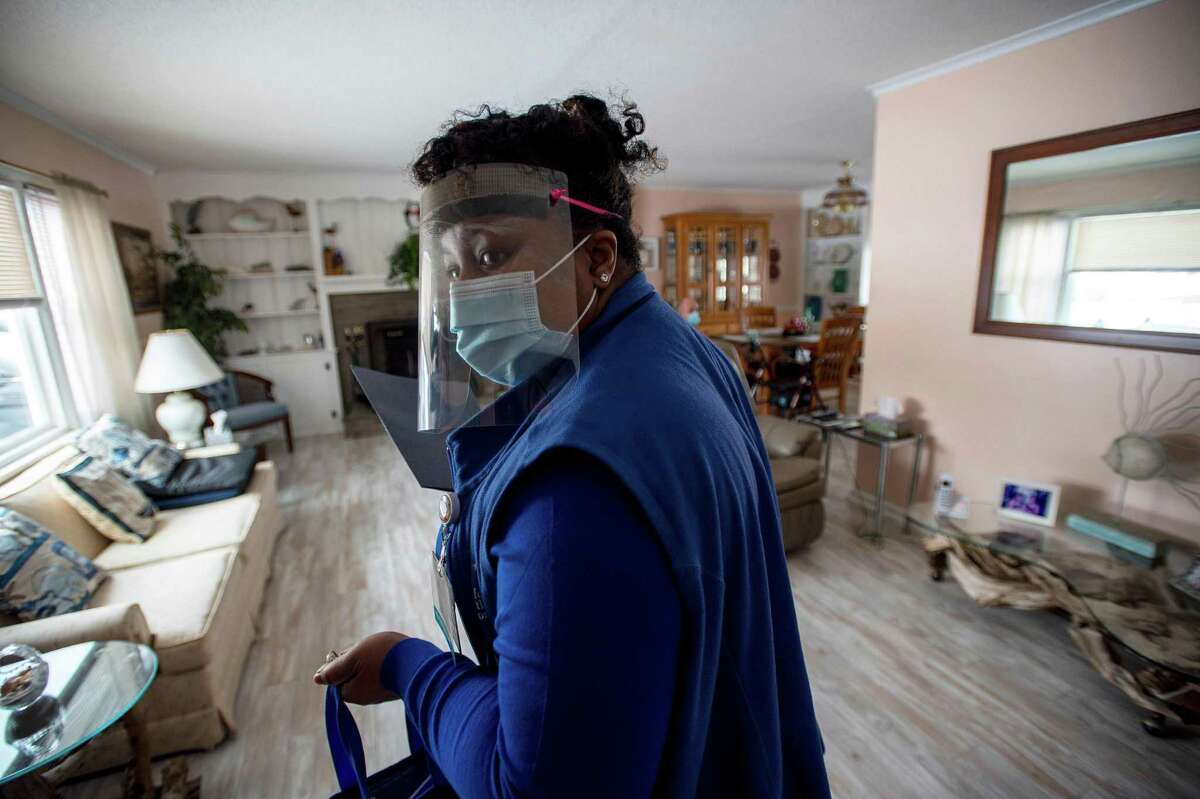 R.N Natalie O'Connor speaks to Rose Mowel before making her way to set up her medical gear on a dining room table to vaccinate Rose and her husband Stanley at their home in Manchester on Feb. 12.