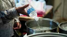 Blinda Whaley pours water into a pan to boil after receiving a case of water and some food from a volunteer group led by Marcel McClinton in the 1900 block of Benson Thursday, Feb. 25, 2021 in Houston. Residents in the Fifth Ward neighborhood received several cases of water and food to help with recovery from the recent winter storms. The residents of the neighborhood have been without water for several days because of broken pipes from the freeze.