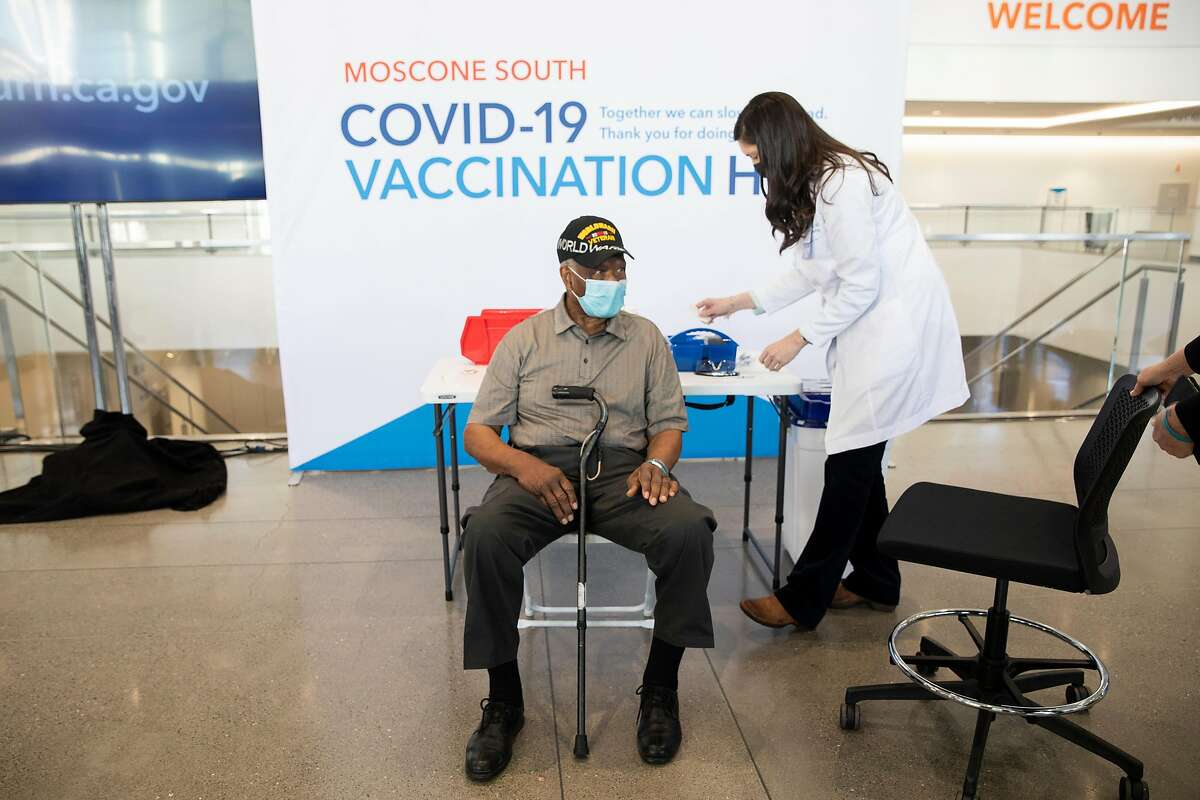 Ezekiel Logan, a 96-year-old World War II veteran, receives his first dose of the Pfizer COVID-19 vaccine ahead of the grand opening of a mass COVID-19 vaccination site at Moscone South in San Francisco, Calif. Thursday, February 4, 2021.