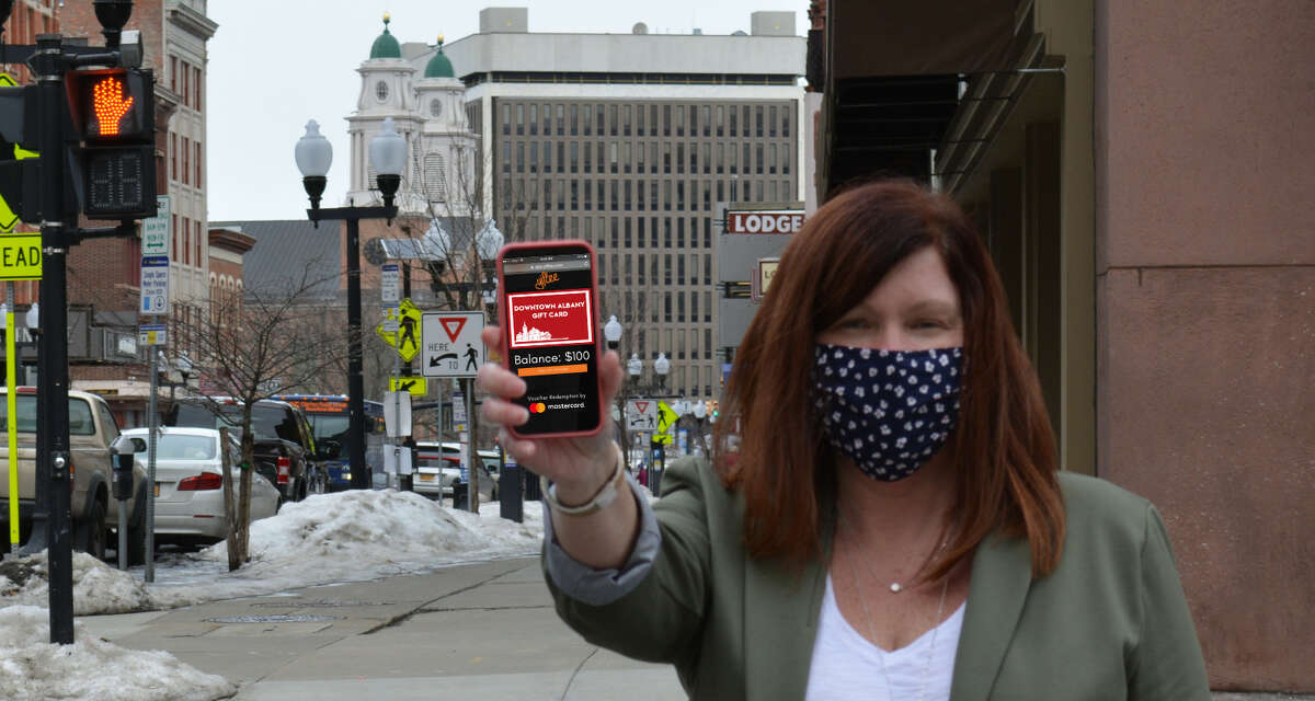 Georgette Steffens, executive director of the Downtown Albany Business Improvement District, stands on NorthPearl Street in Albany holding a phone displaying the new virtual Downtown Albany Gift Card the BID has introduced. (Provided photo.)
