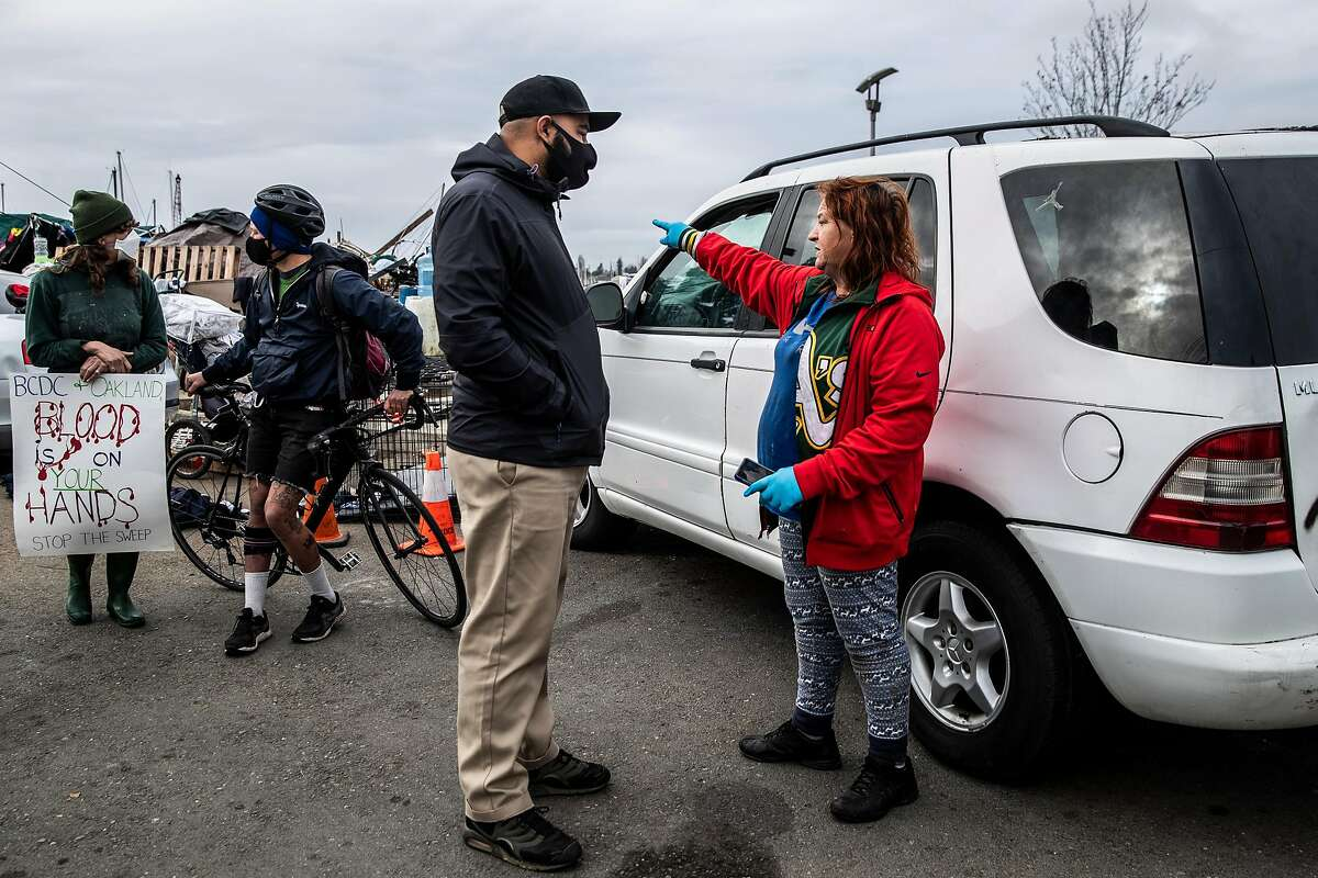 Oakland Homelessness Administrator Daryel Dunston, center, talks with Deanna Riley, who has been living at the homeless encampment at Union Point Park for two years, during a planned clearing by the city in Oakland, California Tuesday, Feb. 9, 2021.