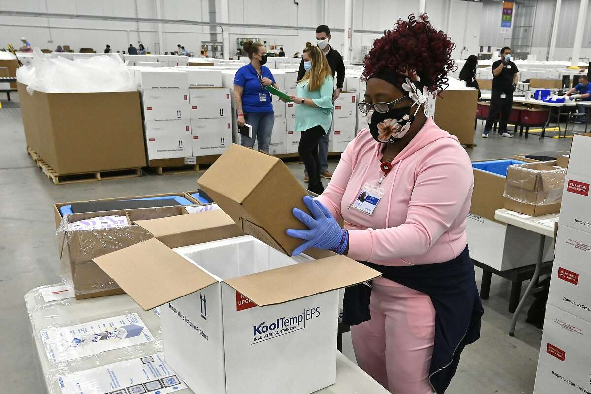 A worker packs the newly approved Johnson & Johnson COVID-19 vaccine into a cooler for shipping from the McKesson Corp. distribution facility in Shepherdsville, Ky.