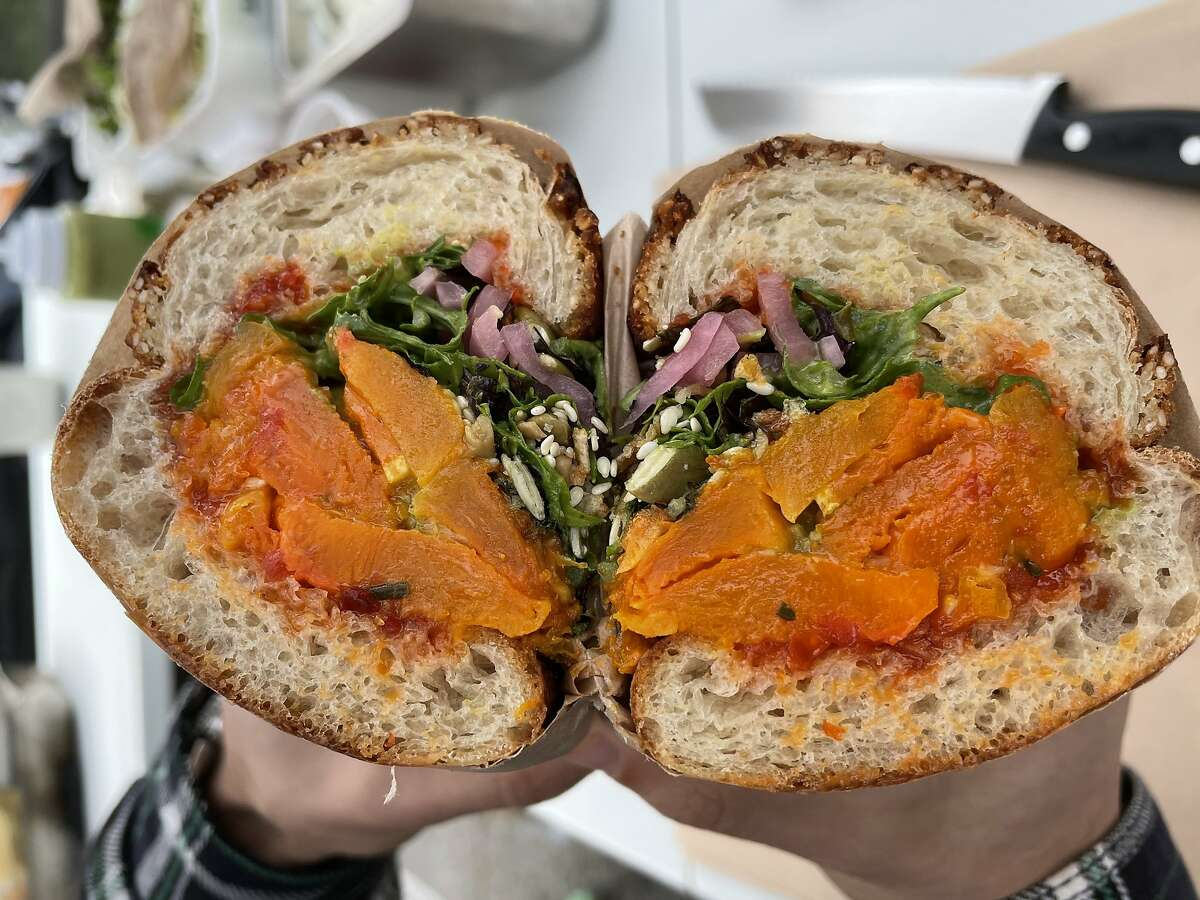 My Sweet & Spicy Butternut, a vegan sandwich from Rozmary Kitchen consisting of butternut squash, Calabrian chili jam, crispy shallots and seeds on Dutch crunch.