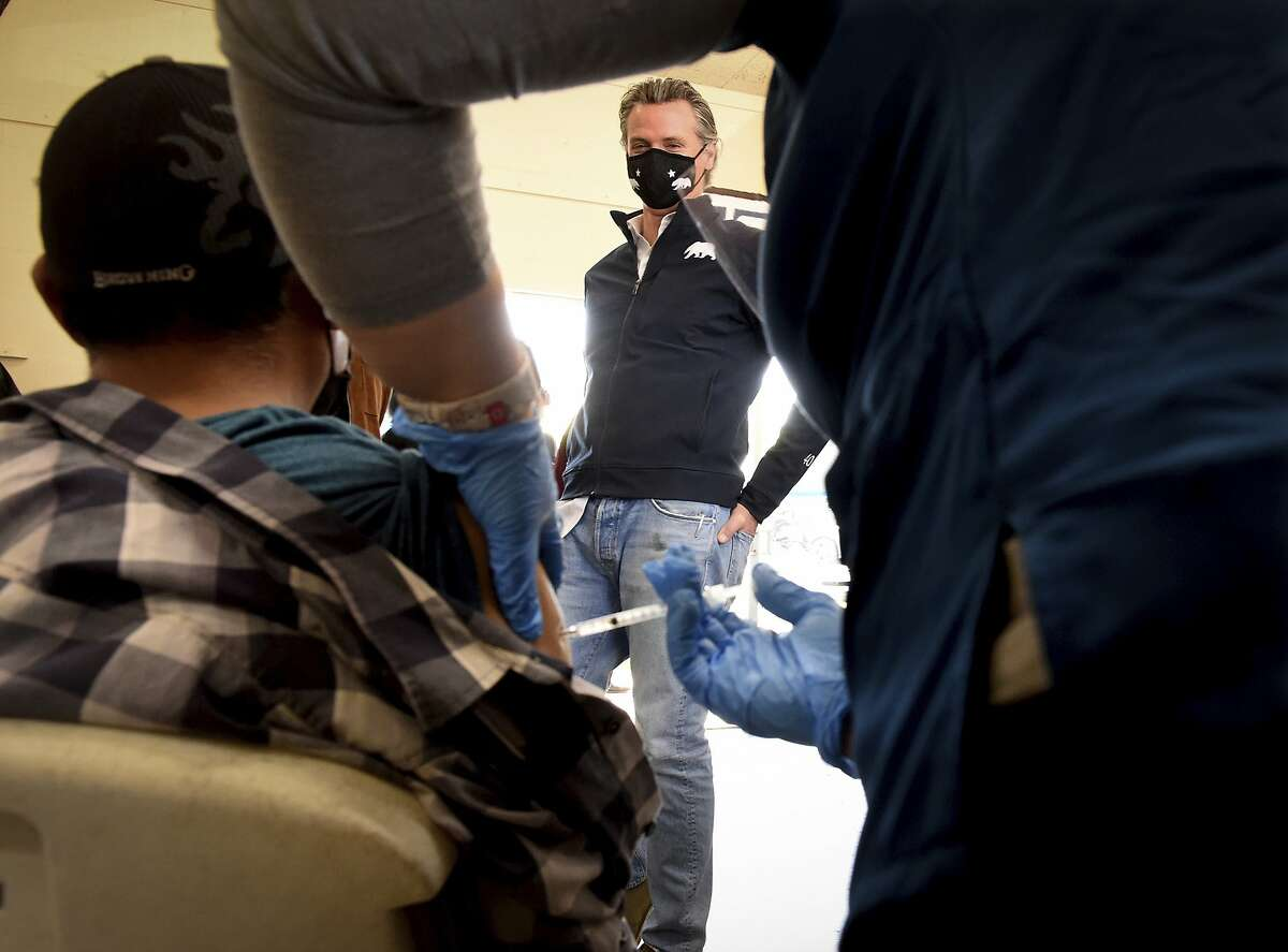 Gov. Gavin Newsom watches farmworker Raul Dominguez receive a Pfizer coronavirus shot in a clinic set up at Fresno's Stanley-Rea Community Center. Farmworkers have been one of the hardest hit communities since the start of the pandemic.