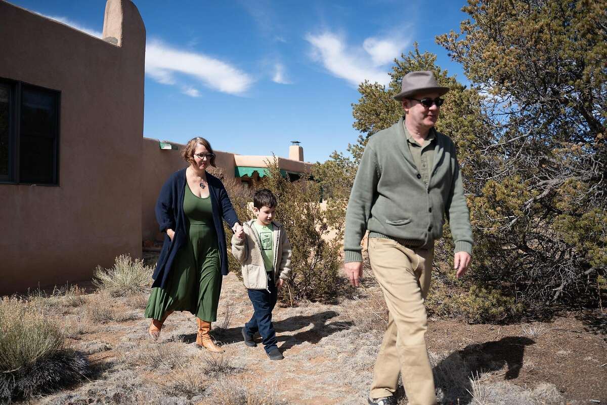 Former San Francisco residents Mark Glaser and Renee Dean, with their son Everett, walk on the trail behind their Santa Fe, N.M., home, where he can work remotely. A Chronicle analysis finds that the outflow of California residents, however, has been much less than often stated.