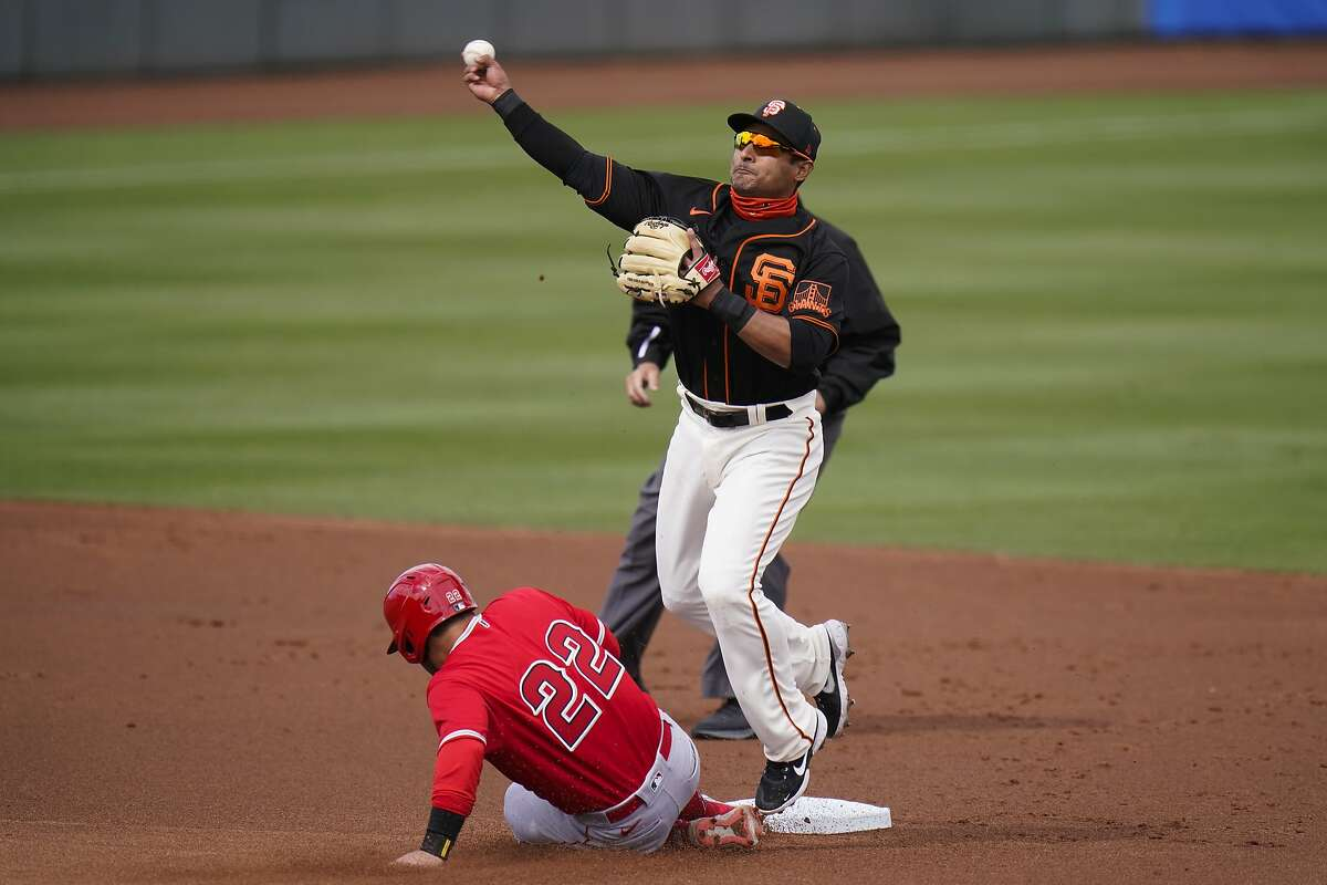 San Francisco Giants second baseman Donovan Solano, top, throws to first base after forcing out Los Angeles Angels' David Fletcher in the first inning of a spring baseball game in Scottsdale, Ariz., Sunday, Feb. 28, 2021. (AP Photo/Jae C. Hong)