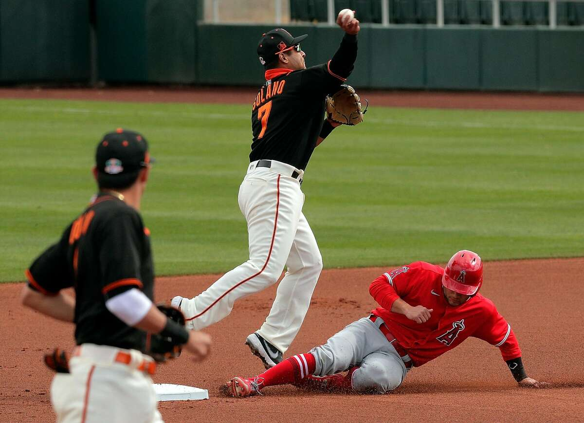 Donovan Solano (7) completes the double play on Jared Walsh (20) on a ball hit by Jo Adell (7) in the first inning as the San Francisco Giants played the Los Angeles Angels at Scottsdale Stadium in Scottsdale, Ariz., on Sunday, February 28, 2021.