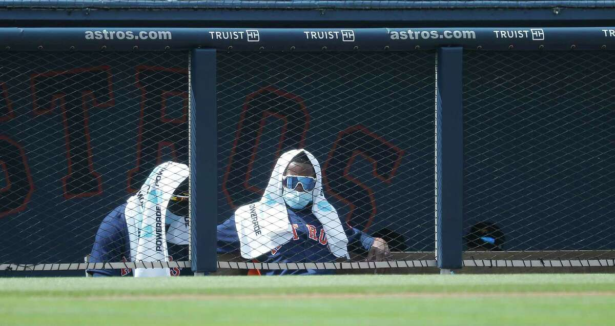 Houston Astros players cover up with towel in the dugout to ward off the sun during the second inning of an MLB spring training game at Ballpark of the Palm Beaches in West Palm Beach, Florida, Monday, March 1, 2021.