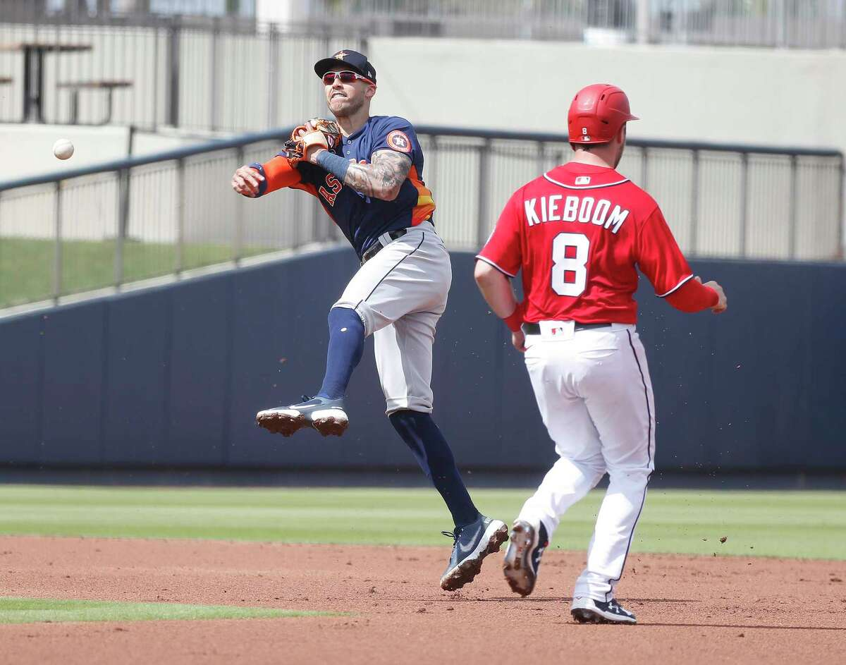 Houston Astros shortstop Carlos Correa (1) tags Washington Nationals Carter Kieboom (8) out at second as he turned the double play on Drew Mendoza during the first inning of an MLB spring training game at Ballpark of the Palm Beaches in West Palm Beach, Florida, Monday, March 1, 2021.