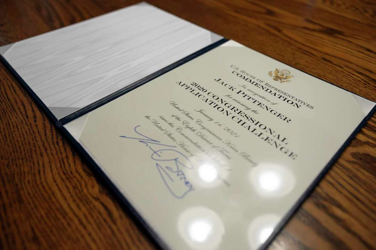 An award is seen in honor of Jack Pittenger in his home in The Woodlands. Pittenger won a congressional app challenge to engage youth in politics and received commendations from the House of Representatives.