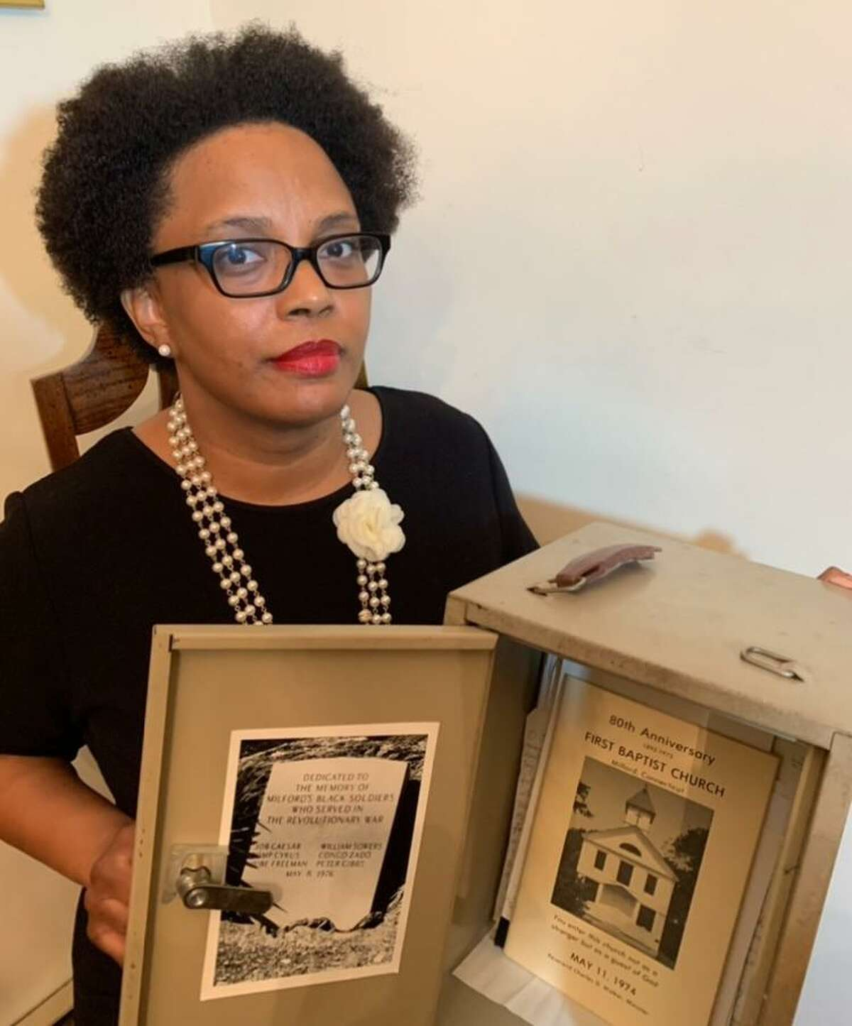 Jennyfer Holmes, the First Baptist Church historian, with the strongbox kept at the church to hold archived items, including the Black Soldiers Memorial marker and an 80th anniversary photo.
