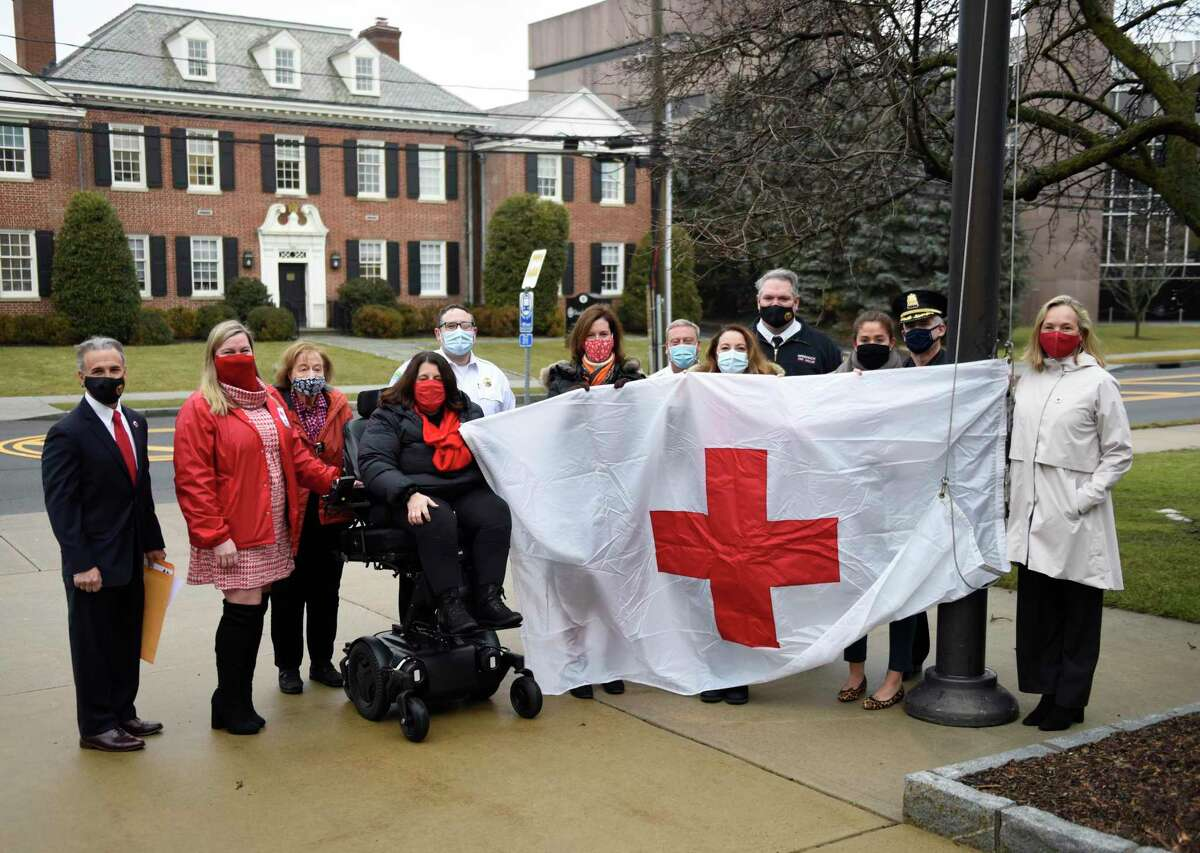 First Selectman Fred Camillo, left, and representatives of the American Red Cross Metro New York North Chapter pose with a Red Cross flag outside Town Hall in Greenwich, Conn. Monday, March 1, 2021. Camillo proclaimed March as Red Cross Month before raising a flag with Red Cross employees and board members.