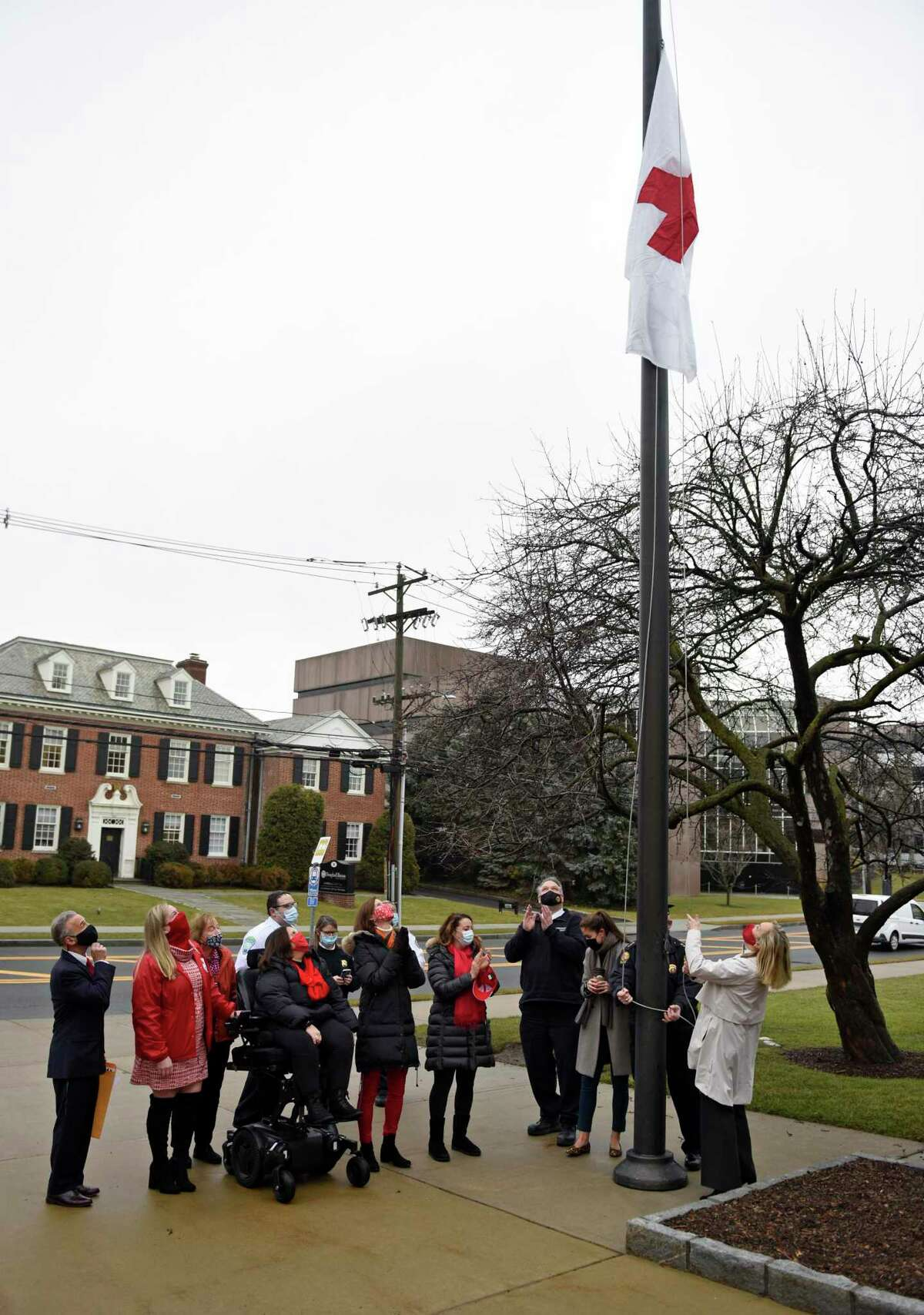 First Selectman Fred Camillo, left, and representatives of the American Red Cross Metro New York North Chapter raise a Red Cross flag outside Town Hall in Greenwich, Conn. Monday, March 1, 2021. Camillo proclaimed March as Red Cross Month before raising a flag with Red Cross employees and board members.