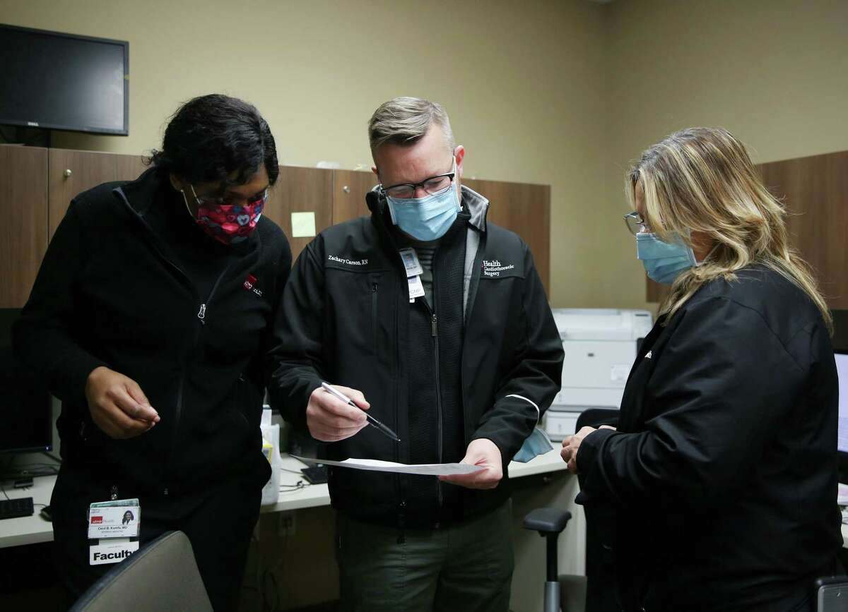 UTMB home health care staff Dr. Cecil Kumfa, nurse practitioners Zachary Carson and Tammie Michael go over the patient list for home delivery of the second dose of the Pfizer COVID vaccines to patients in League City, Texas on Thursday, Feb. 18, 2021.