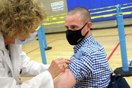 Benjamin Powers, Head of School at the Southport School, in Fairfield, receives a COVID-19 vaccination at the Bigelow Center clinic in Fairfield, Conn. March 1, 2021.