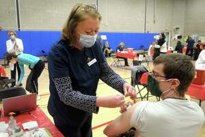 Jill Mitchell, the head nurse administrator for the Town of Fairfield, places a band aid on the arm of David Kean, a music teacher from Rochambeau Middle School, in Southbury, following his COVID-19 vaccination at the Bigelow Center clinic in Fairfield on Monday.