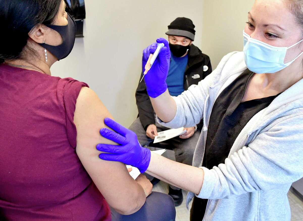 Michele Sbrega, a family nurse practitioner at the Fair Haven Community Health Care Covid Vaccination Clinic on Grand Avenue in New Haven, left, vaccinates Irma Reyes, 58, of New Haven, left, as her already vaccinated husband Jose Reyes, 27, center, waits.