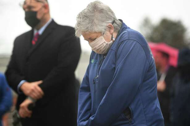 Stratford Health Director Andrea Boissevain bows her head during a remembrance vigil for COVID-19 victims and survivors on the one year anniversary of the first U.S. death from the virus outside City Hall in Stratford, Conn. on Monday, March 01, 2021.