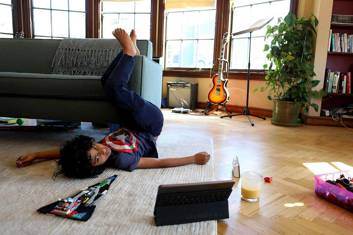 Jeevan Guha, 6, relaxes on the living room floor as he attends his West Portal Elementary Zoom first-grade class.