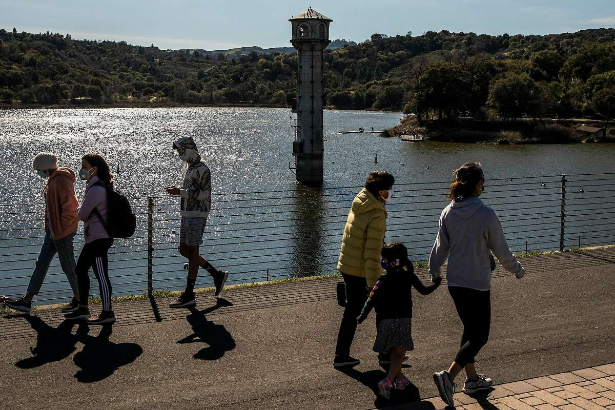 On Sunday, visitors walk and scooter along Lafayette Reservoir with its water outlet tower in the background.