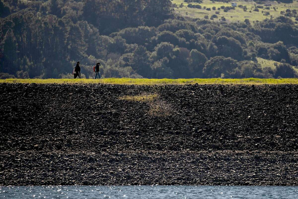 Visitors hike on Oursan Trail along Briones Reservoir in Orinda on Sunday - many reservoirs in the state are below capacity because of two dry winters.