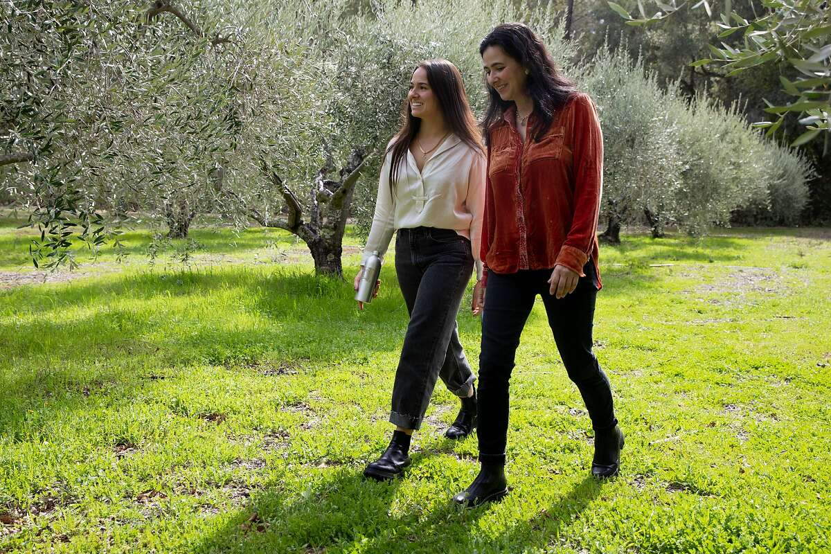 Marcela Hernandez (left) and her mother, Ana Hernandez, walk through an olive grove at their Grove 45 olive oil company in St. Helena.