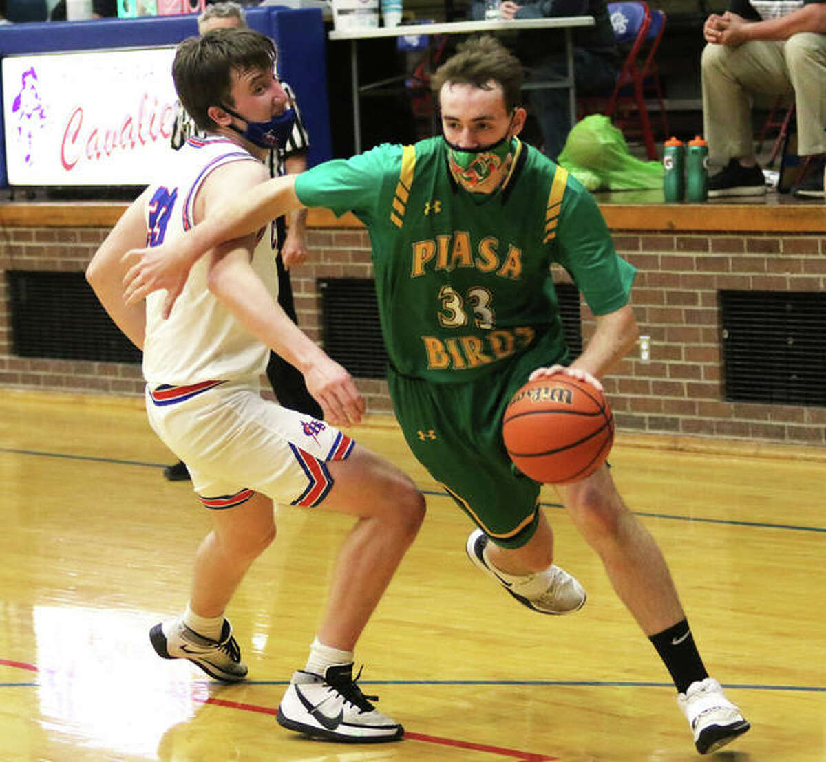 Southwestern's Addis Moore (right) drives past Carlinville's Aaron Wills in Wednesday's SCC game at Carlinville.
