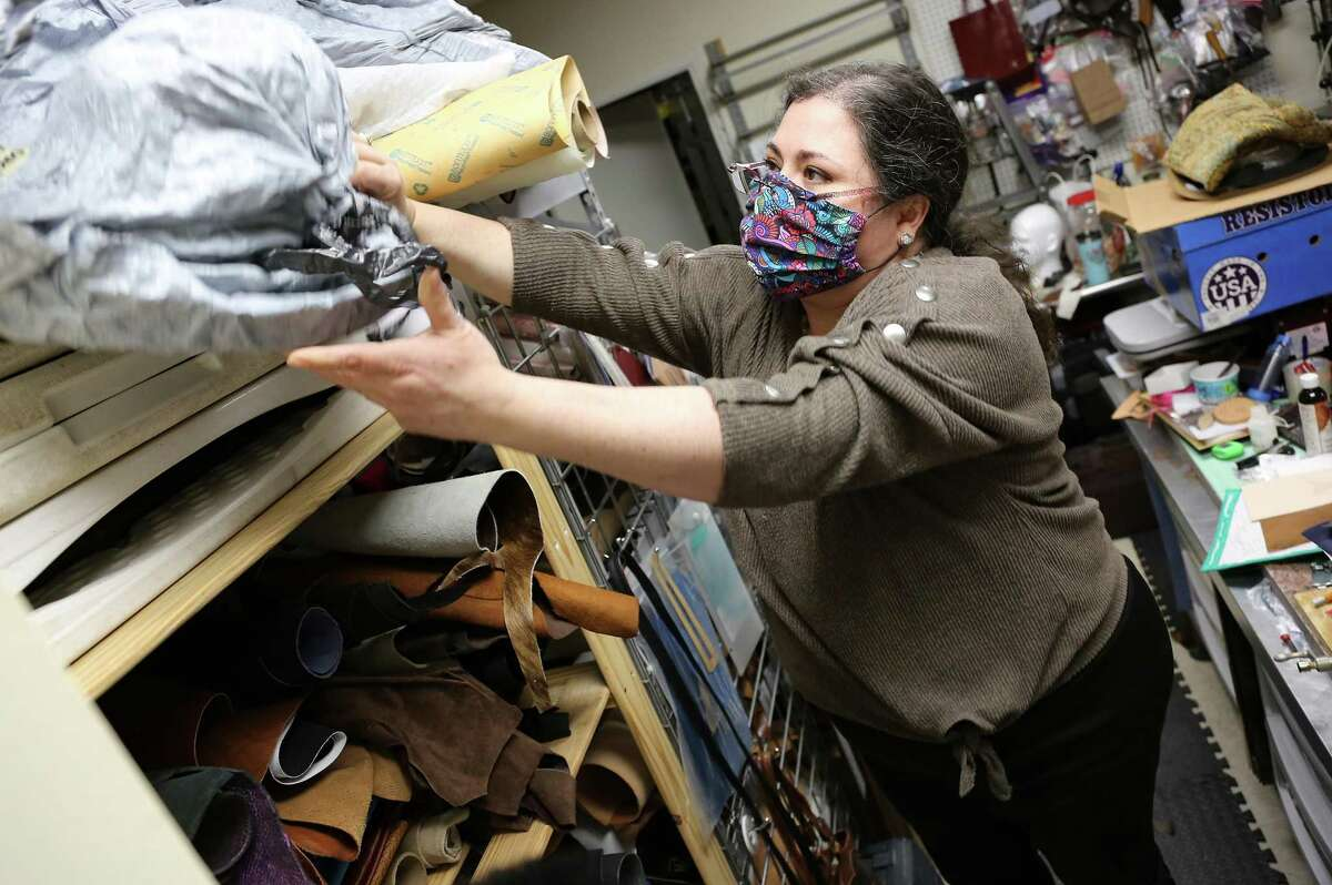 Tania Alejandra, owner of TexasLuxuryGoods, works on organizing her down-sized workspace in Houston on Friday, Feb. 5, 2021. Alejandra's landlord let her downsize her space to save money.