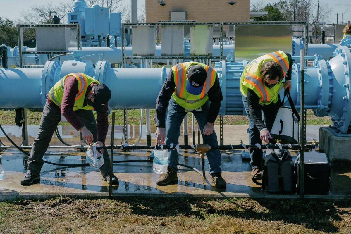 Employees of San Antonio Water System fill containers at a water distribution center after a weeklong icy storm. To the relief of ratepayers, SAWS said it will charge all customers the lower of two amounts on their next bill: either the total for February or the total from January.