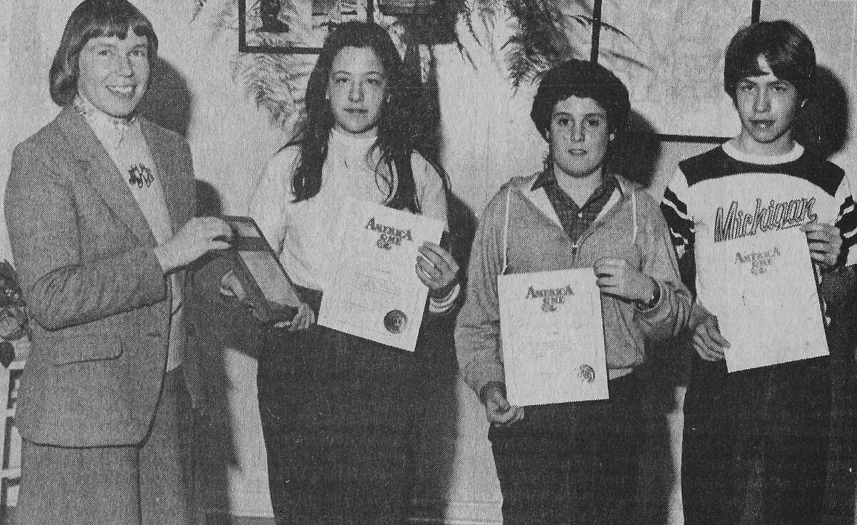 (From left) Marcia Korwin presents three Manistee Junior High School students with certificates from the American and Me essay contest. The students are:Susan Peterson,Paul Brown andJoel Nielson. The photo was published in the News Advocate on March 2, 1981. (Manistee County Historical Museum photo)