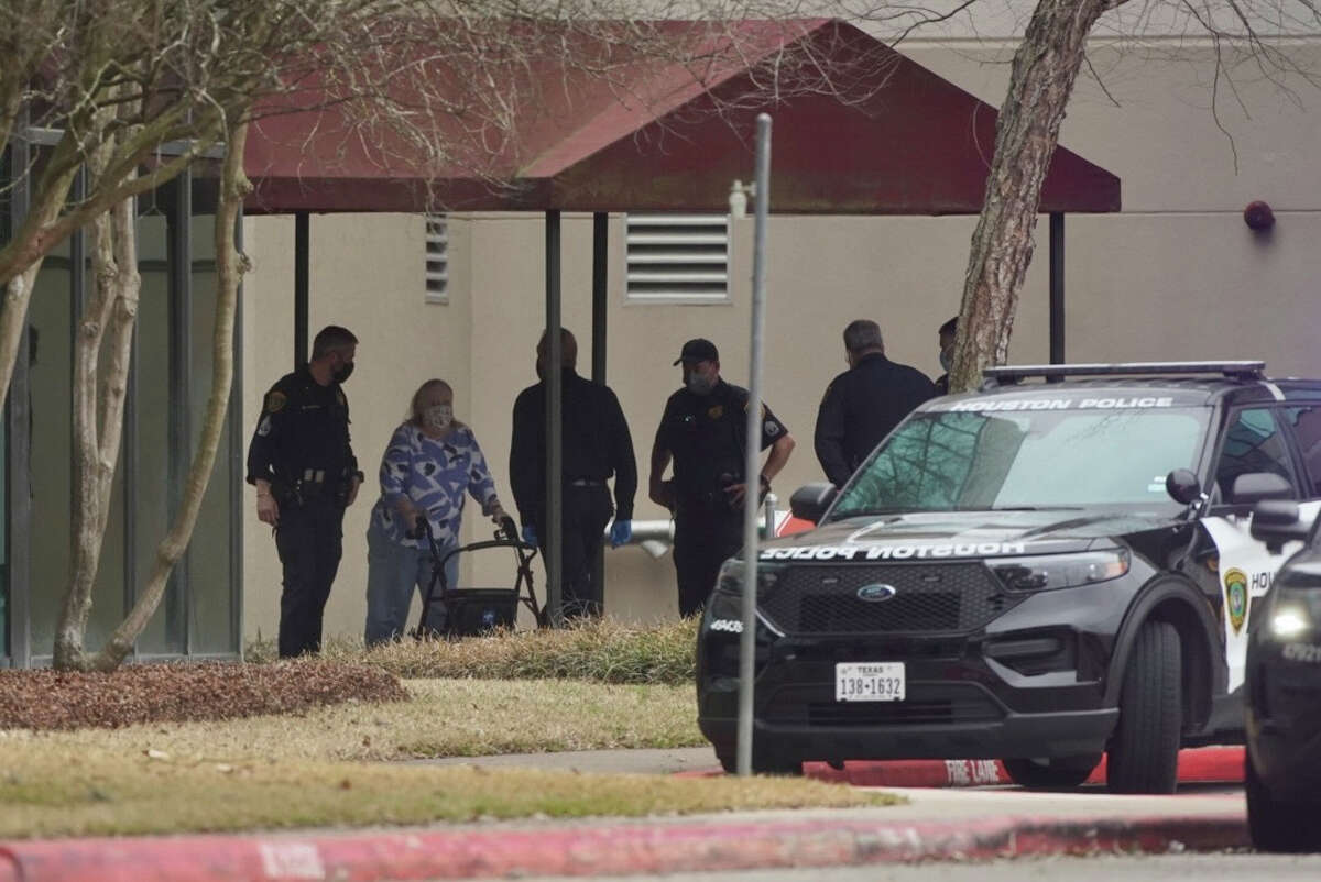 People and police walk through an entrance of a medical office building after reports of a shooting at the HCA Houston Healthcare West Houston Doctors Center on Monday afternoon, March 1, 2021, in Houston.
